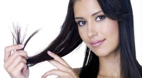 Девушка показывает секущиеся волосы
